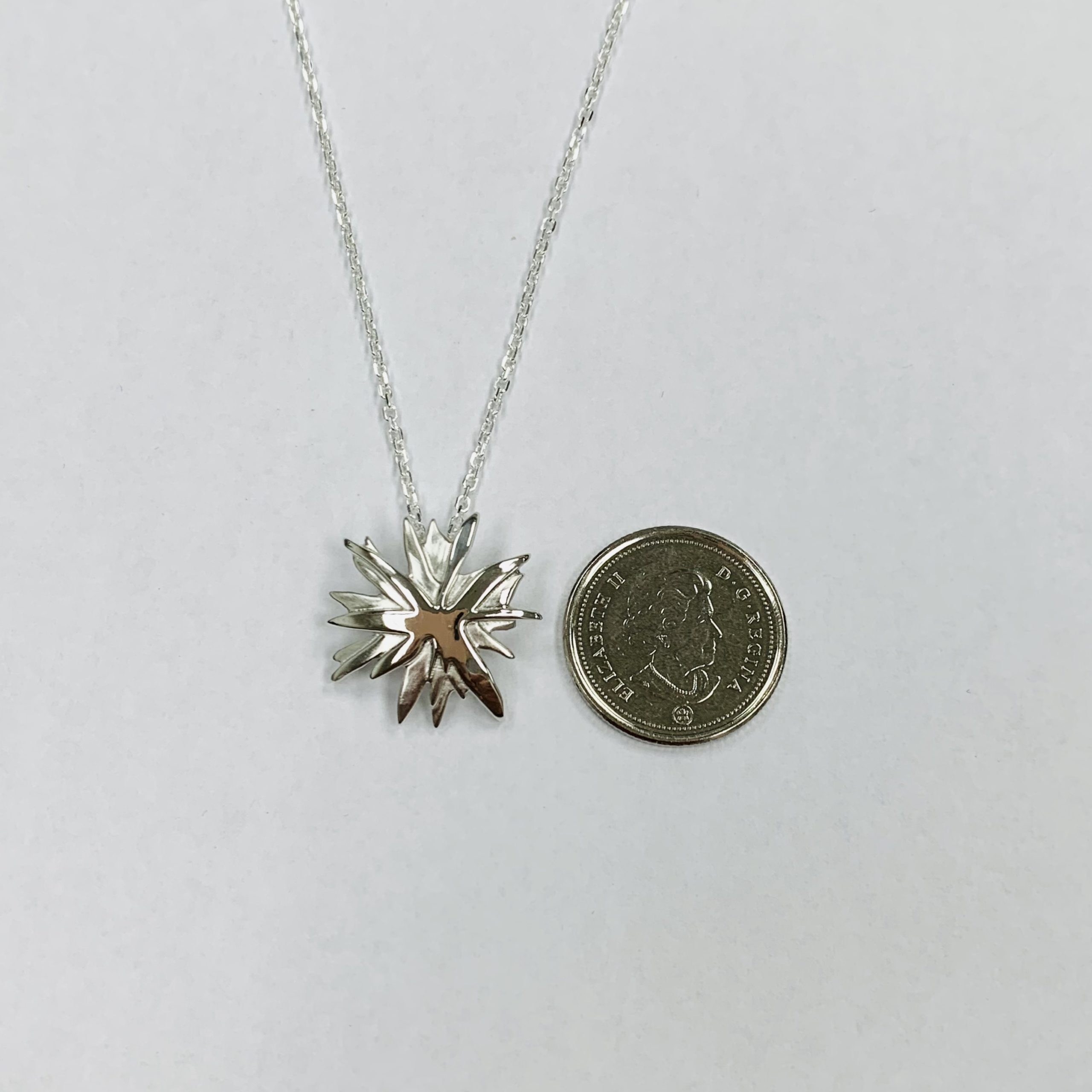 Mining Matters 'The Spark' Pendant shown side by side with a Canadian dime for size reference